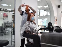 Senior stylist Robert Brooks cuts the hair of Carmen Smith at the Lazarou salon in Cardiff, Wales (Ben Birchall/PA)