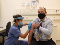 Dr Michael McBride receives his first dose of the Oxford/AstraZeneca vaccine (Liam McBurney/PA)