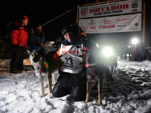 Dallas Seavey poses with his dogs after crossing the finish line (Marc Lester/Anchorage Daily News via AP)