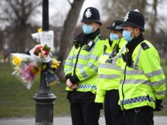 Police officers stand next to floral tributes left at the bandstand in Clapham Common, London, for murdered Sarah Everard. Serving police constable Wayne Couzens, 48, appeared in court on Saturday charged with kidnapping and murdering the 33-year-old marketing executive, who went missing while walking home from a friend's flat in south London on March 3 (Kirsty O'Connor/PA)