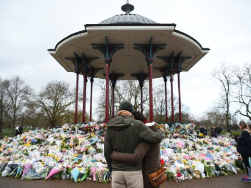 People stand next to floral tributes left at the band stand in Clapham Common, London (Kirsty O'Connor/PA)