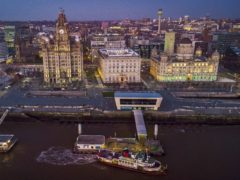 The Mersey ferry leaves its terminal in front of the Royal Liver Building in Liverpool (Peter Byrne/PA)