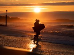 Bodyboarders make their way into the sea as the sun rises over Boscombe beach in Dorset (Andrew Matthews/PA)