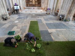 Gardeners work on a green meadow cross in the Nave of Winchester Cathedral (Andrew Matthews/PA)