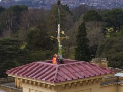 Workers install the newly restored Victorian weathervane on the 90ft clock tower at English Heritage's Osborne House in East Cowes, on the Isle of Wight (Steve Parsons/PA)