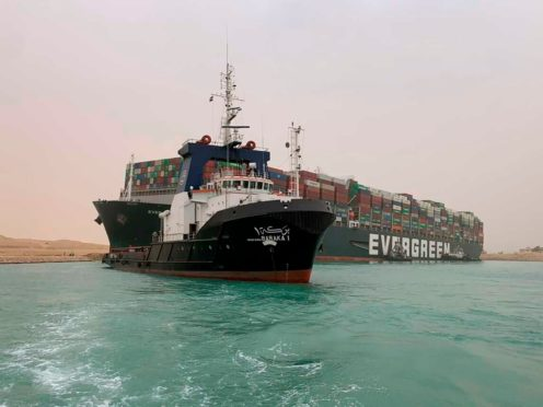 A boat navigates in front of a cargo ship, Ever Given, after it became wedged across Egypt's Suez Canal and blocked all traffic in the vital waterway (Suez Canal Authority via AP)