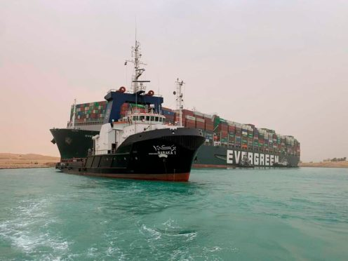 Suez Canal Authority boats come to the assistance of the Ever Given on Wednesday (Suez Canal Authority/AP)
