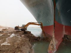 Workers attempt to dig out the Ever Given (Suez Canal Authority/AP)