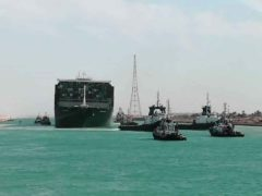 The Ever Given is accompanied by tugboats as it moves in the Suez Canal (Suez Canal Authority/AP)