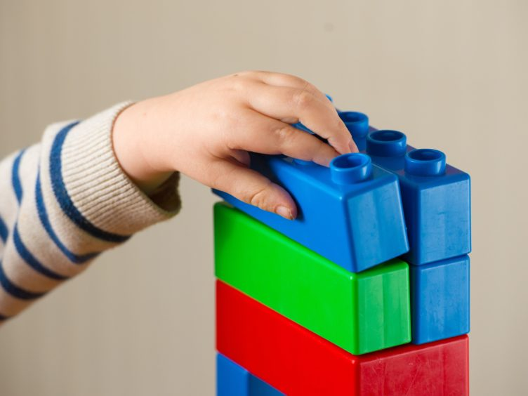 A preschool age child plays with plastic building blocks (PA)