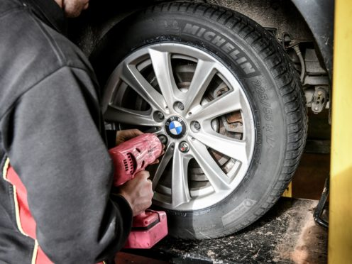 A mechanic replaces a car tyre
