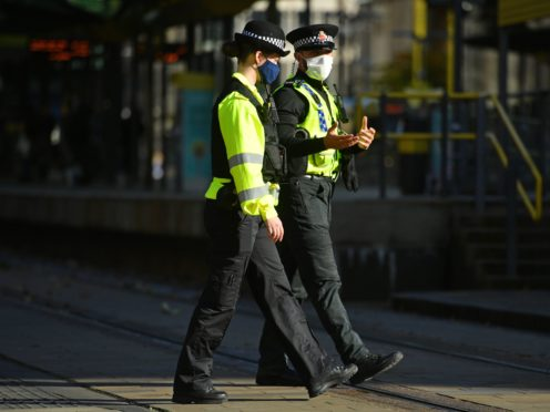 Police officers wearing face masks in St Peter's Square, Manchester (Jacob King/PA)