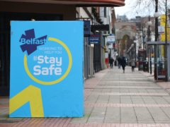 A public information sign on an empty street in Belfast (Liam McBurney/PA)