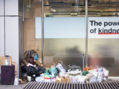 A homeless person sits in a window in the City of London (Victoria Jones/PA)
