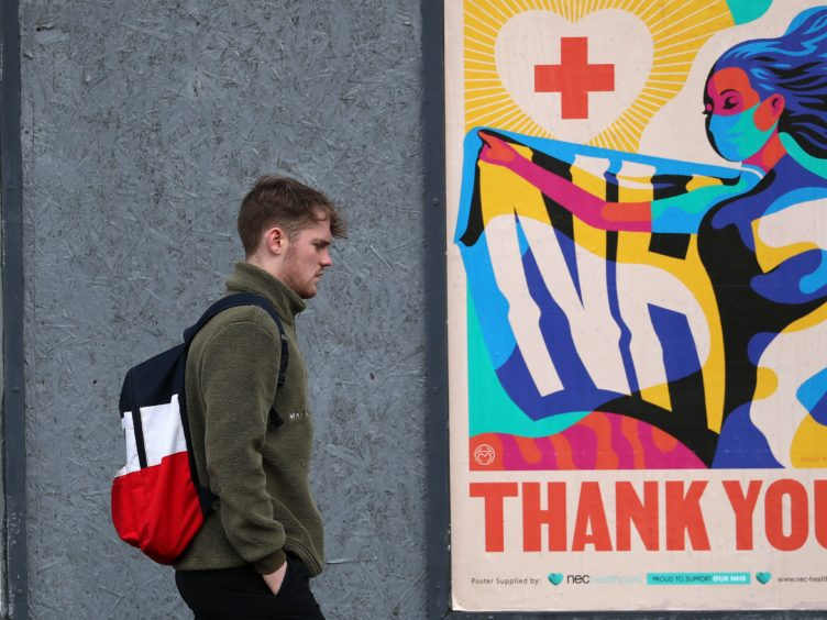 A person walks passed an advertising board in Glasgow showing a Thank You NHS poster (Andrew Milligan/PA)