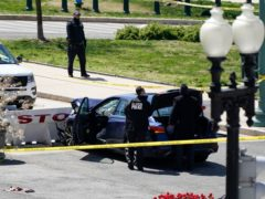 US Capitol Police officers near a car that crashed into a barrier on Capitol Hill (J Scott Applewhite/AP)