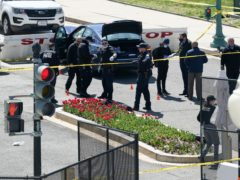 Police officers investigate near a car that crashed into a barrier at the US Capitol in Washington (J Scott Applewhite/AP)