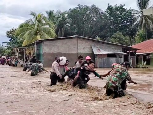 Soldiers and police officers help residents to cross a flooded road in Malaka Tengah, East Nusa Tenggara province, Indonesia (AP)