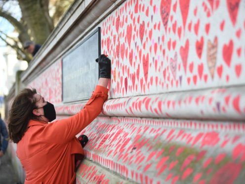 A woman takes part in the final stages of painting approximately 150,000 hearts on to the National Covid Memorial Wall on the Embankment in London (Victoria Jones/PA)