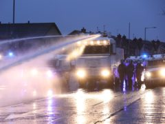The PSNI use a water cannon on the Springfield Road, during further unrest in Belfast (Liam McBurney/PA)