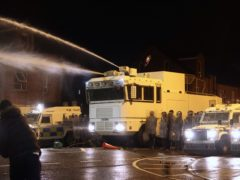 Objects are thrown towards PSNI officers and the water canon on Springfield Road in Belfast (PA)