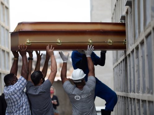 A coffin is placed into a niche by cemetery workers at the Inahuma cemetery in Rio de Janeiro, Brazil (Silvia Izquierdo/AP)