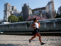 A woman jogs in front of Notre Dame cathedral (AP)