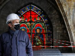 French President Emmanuel Macron stands by a stained glass window under the damaged vaults during a visit at the reconstruction site of the Notre-Dame de Paris cathedral, Thursday April 15, 2021. Two years after a fire tore through Paris' most famous cathedral and shocked the world, French President Emmanuel Macron on Thursday visited the building site that Notre Dame has become to show that French heritage has not been forgotten despite the coronavirus. (Ian Langsdon, Pool via AP)