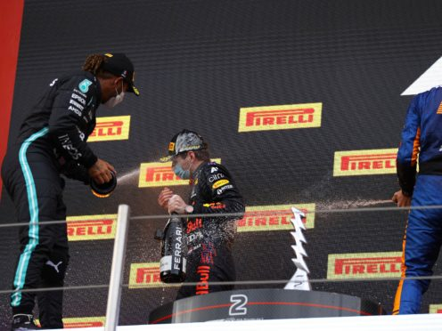 Lewis Hamilton, left, sprays race winner Max Verstappen with champagne on the podium (Bryn Lennon/AP)