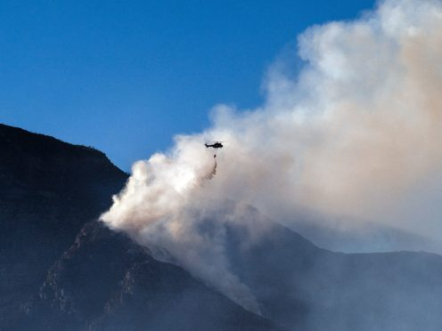A South African military helicopter drops water on the top of Table Mountain in Cape Town (Jerome Delay/AP)