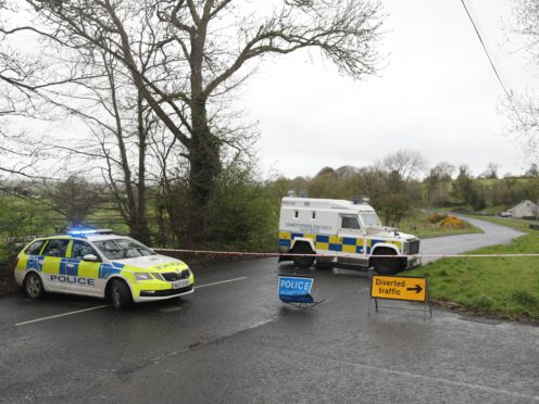 PSNI vehicles block a road near the scene of the incident (Niall Carson/PA)