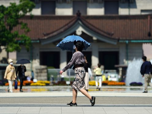 A woman wearing a protective mask to help curb the spread of the coronavirus walks at a park in Tokyo (Eugene Hoshiko/AP)