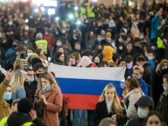 People hold a Russian flag during the opposition rally in support of jailed opposition leader Alexei Navalny in Moscow (Pavel Golovkin/AP)