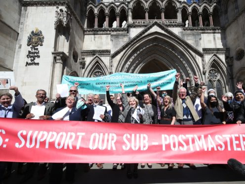 Former post office workers celebrate outside the Royal Courts of Justice, London (Yui Mok/PA)