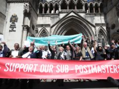 Former post office workers celebrating outside the Royal Courts of Justice (Yui Mok/PA)