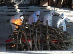 Family members of a Covid-19 victim perform the last rites at a crematorium in Jammu on Monday as the pandemic continued to worsen in India (Channi Anand/AP)