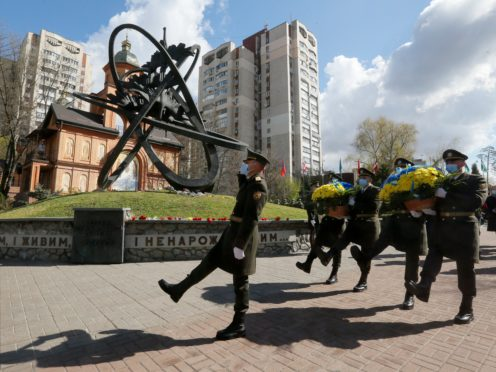 Guards of Honor march to lay a flower wreath at Chernobyl's victim monument in Ukraine's capital Kyiv, Ukraine, Monday, April 26, 2021. April 26 marks the 35th anniversary of the Chernobyl nuclear disaster. A reactor at the Chernobyl nuclear power plant exploded on April 26, 1986, leading to an explosion and the subsequent fire spewed a radioactive plume over much of northern Europe. (AP Photo/Efrem Lukatsky)