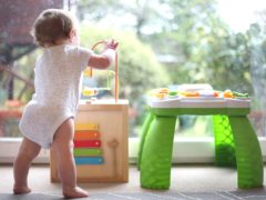 A baby boy playing with an activity table (Philip Toscano/PA)