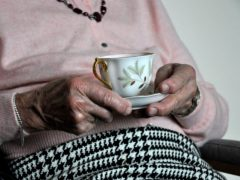 An elderly woman holding a cup of tea (Kirsty O'Connor/PA)