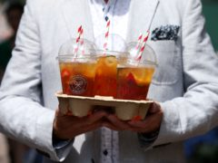 A spectator carries a drinks holder containing Pimms at the All England Lawn Tennis and Croquet Club, Wimbledon.