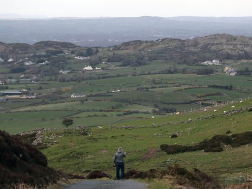 A man looks across the border between the Republic of Ireland and Northern Ireland from Edentober in Co Louth to Newry in Co Down.