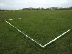 Goalposts lie on a pitch (Steven Paston/PA)