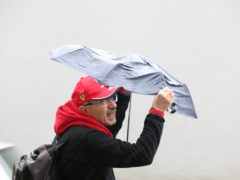 A man struggles with an umbrella in the wind and rain in London (PA)