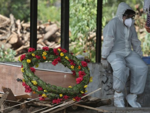 A wreath lies on the coffin of a Covid-19 victim in India (Channi Anand/PA)