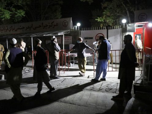 Afghans wait outside to see their relatives after the suicide blast (AP)