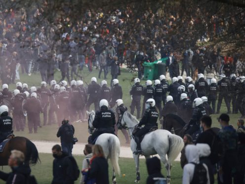 "Police attempt to disperse gatherers at the Bois de la Cambre park during a party called ""La Boum 2"" in Brussels, Saturday, May 1, 2021. Police put on extra patrols Saturday to monitor the gathering which is being held in defiance of Belgium's current COVID-19 regulations. (AP Photo/Olivier Matthys)"
