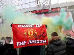 A fan holds up a banner as they protest against the Glazer family (Barrington Coombs/PA)