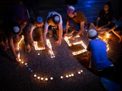 Israeli youths light candles in memory of the 45 ultra-Orthodox Jews killed in a stampede at a religious festival on Friday, during a vigil in Tel Aviv, Israel (Oded Balilty/AP)