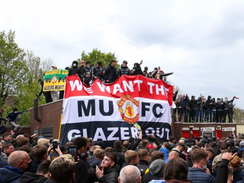 Fans hold up banners as they protest against the Glazer family, owners of Manchester United, before their Premier League match against Liverpool at Old Trafford, Manchester (Barrington Coombs/PA)