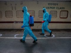 Health workers in personal protective equipment sanitise a train prepared as a Covid-19 care centre at a railway station in Gauhati, India (Anupam Nath/AP)